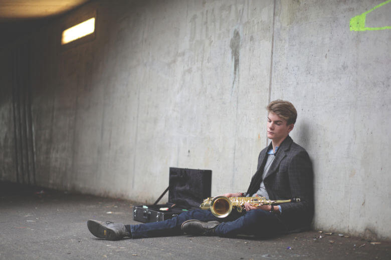 man-sitting-down-with-saxophone-780x520